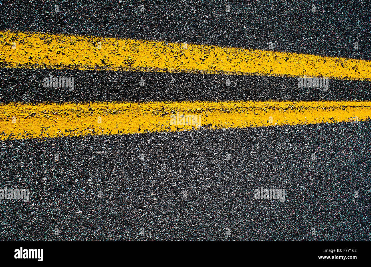 Closeup of a double yellow line on an asphalt road, horizontal. - Stock Image