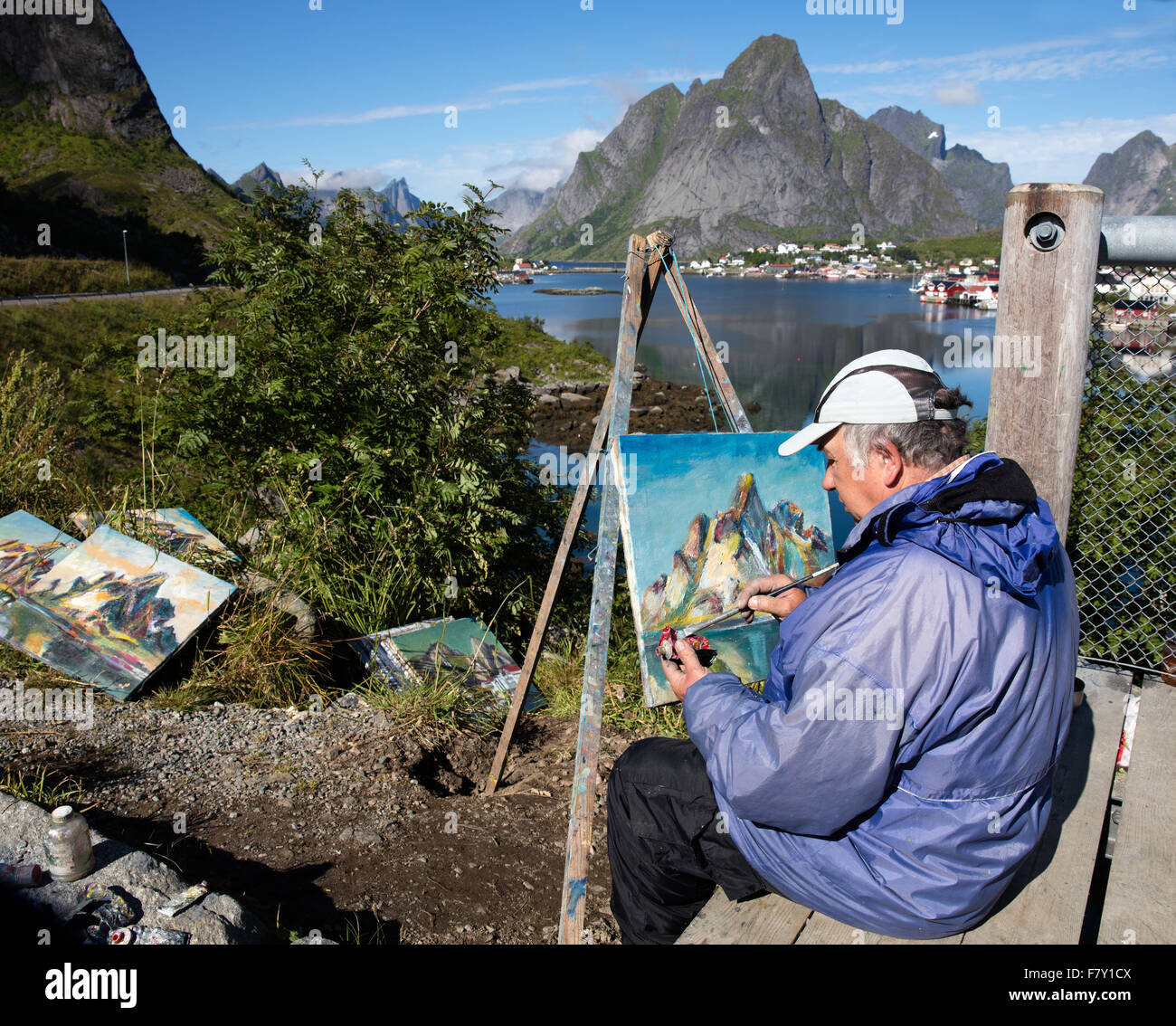 An artist with his paintings of the harbour town of Reine and Olstinden mountain in th Lofoten Islands Norway Stock Photo