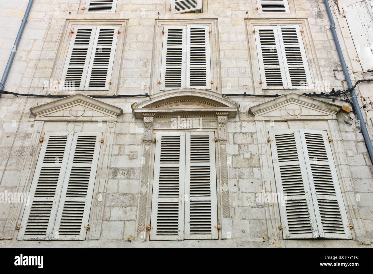 Closed shuttered windows in a building facade, Saintes, Poitou-Charentes, France - Stock Image