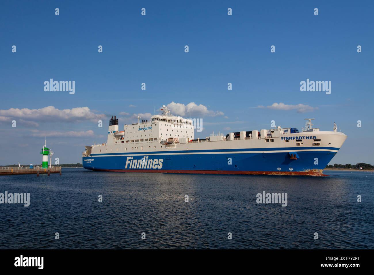 Ro-ro passenger ferry Finnpartner from Finnlines passing lighthouse Travemünde Nordmole, Travemuende, Lübeck, - Stock Image