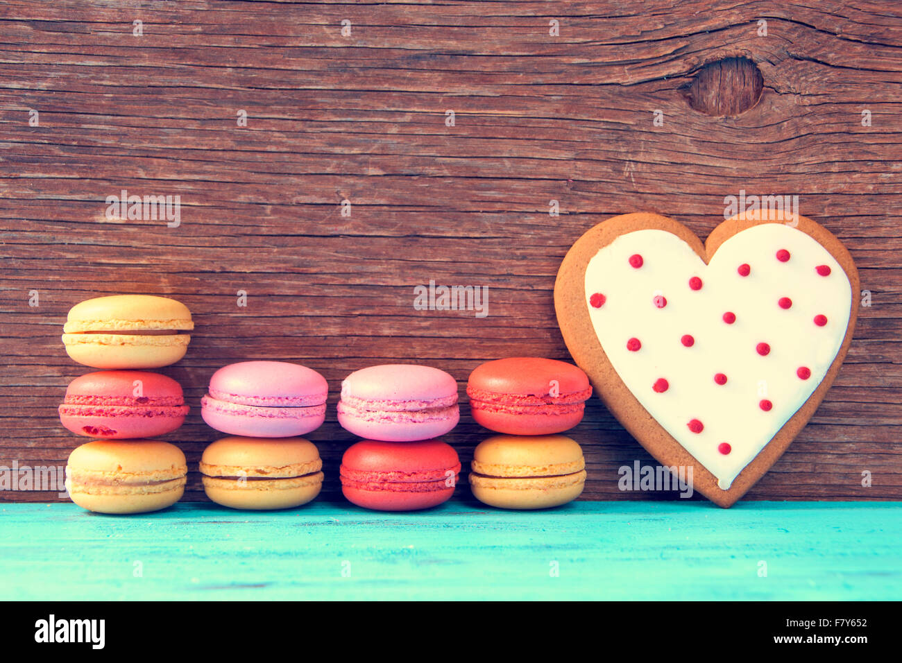 some appetizing macarons with different colors and flavors and a homemade heart-shaped cookie on a blue wooden surface, - Stock Image