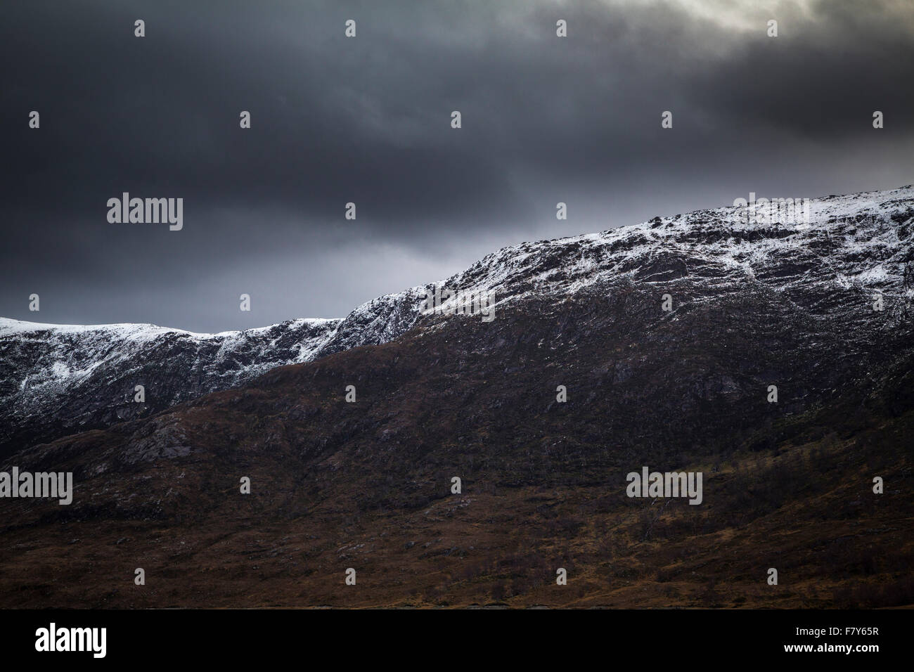Storm clouds over the Scottish Highlands with a light dusting of snow, Kintail, Scotland - Stock Image