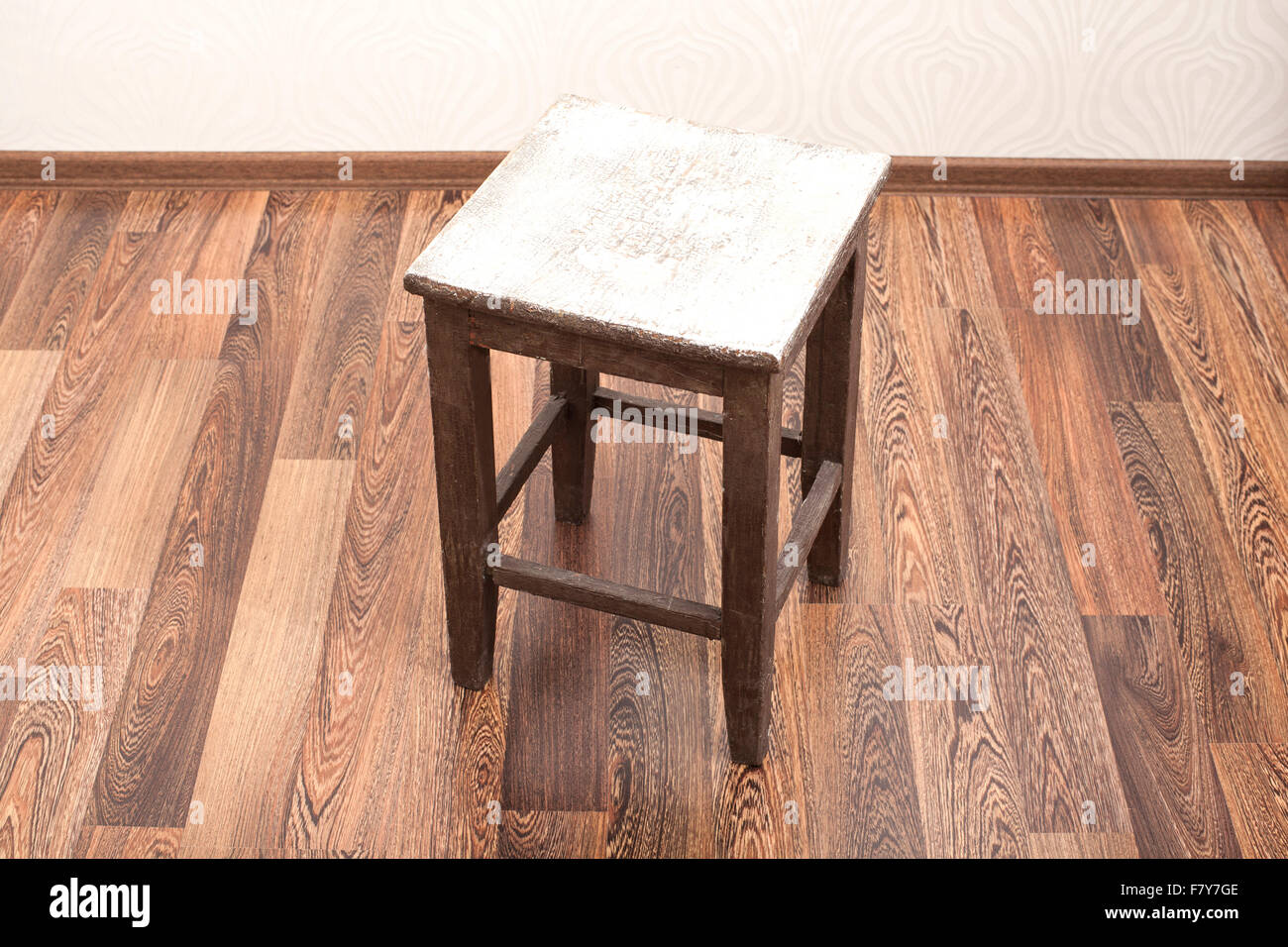 Rustic wooden stool in room - Stock Image