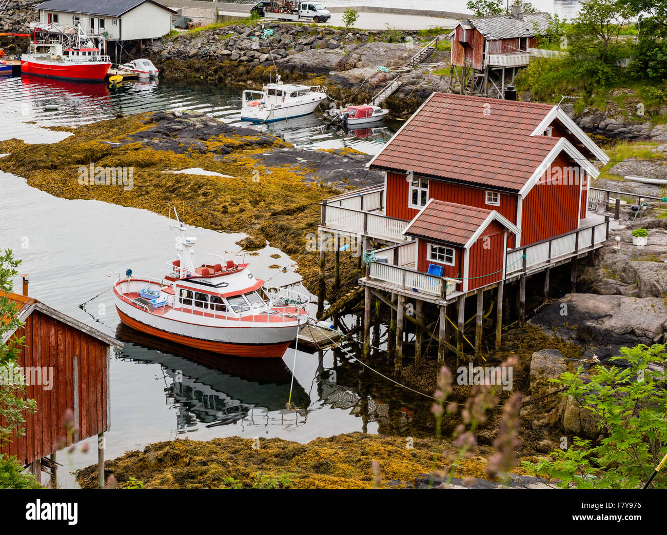 Small house on stilts and small fishing boat moored alongside at Moskenes in the western Lofoten Islands Norway - Stock Image
