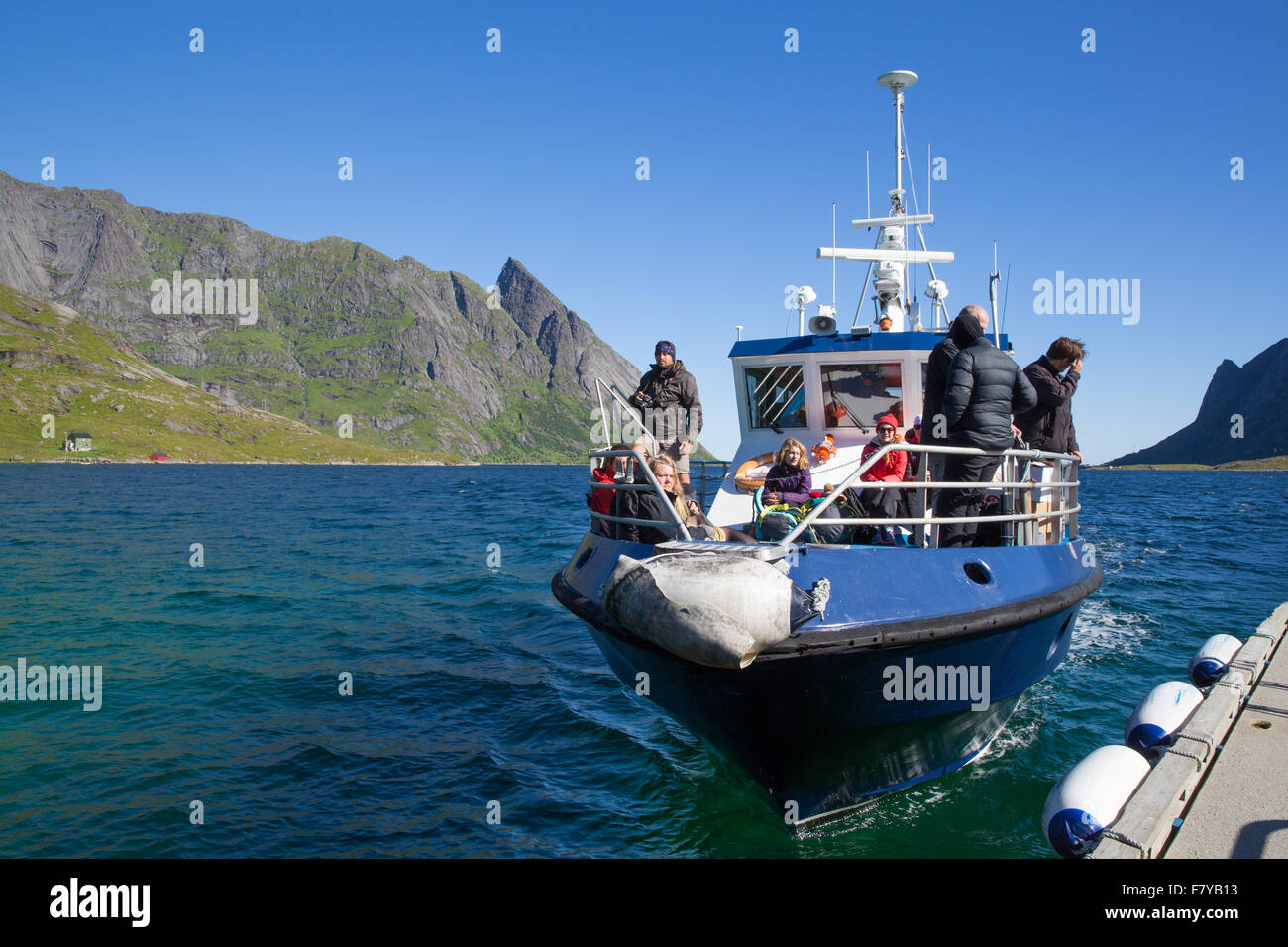 Passenger ferry boat arriving at the jetty of Vindstad on Bunesfjord near Reine - western Lofoten Islands Norway - Stock Image