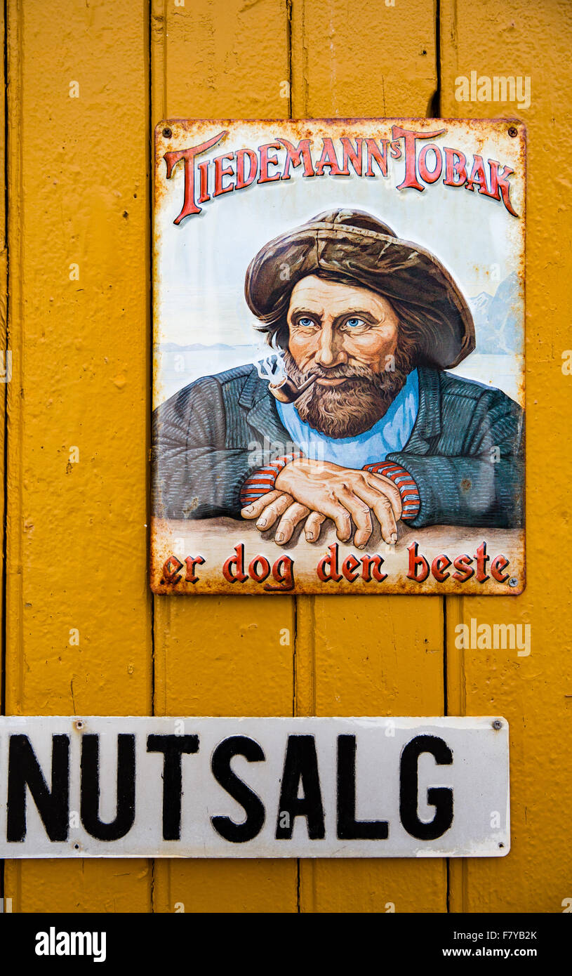Antique enameled tobacco advertisement at the heritage village of Nusfjord in the Lofoten Islands with pipe smoking - Stock Image