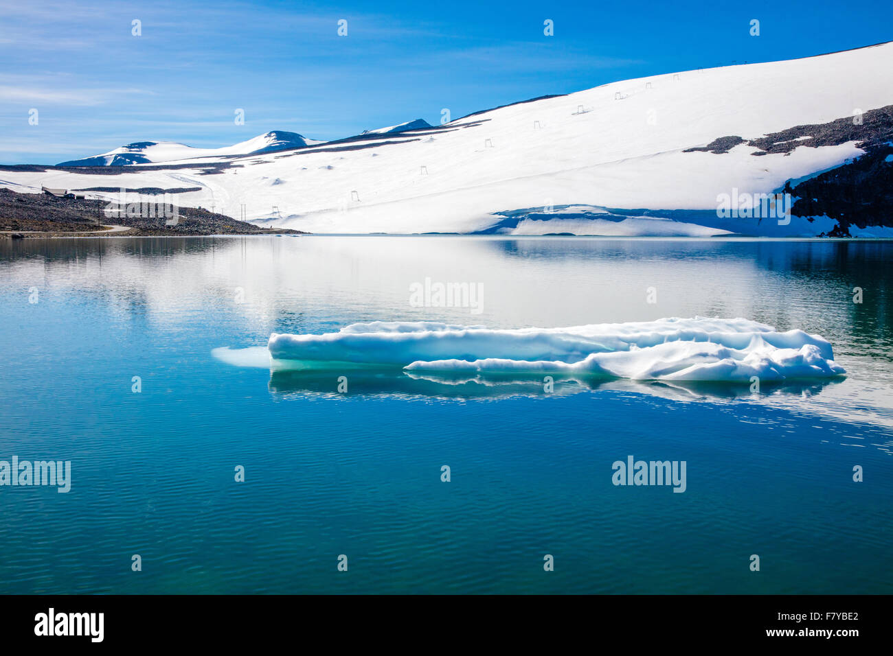 Mountain lake with small summer icegerg near Galdhopiggen the highest mountain in Norway - Stock Image