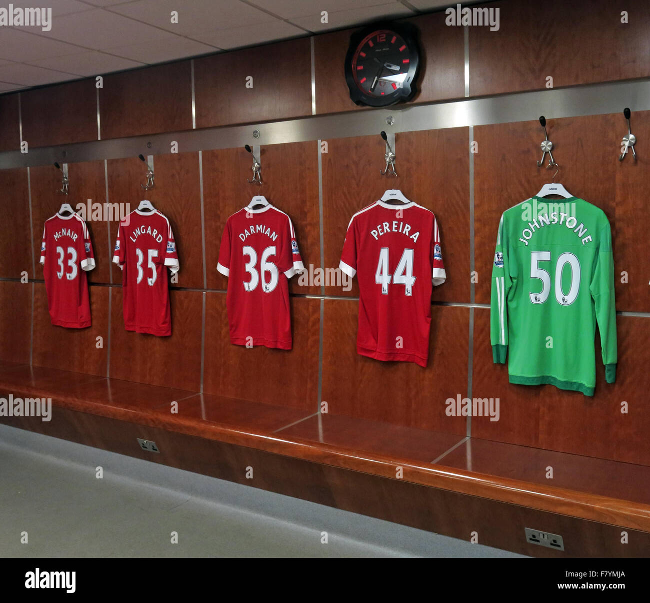 Mix of MUFC shirts hanging up in MUFC dressing room, with MUFC clock, Old Trafford, Manchester - Stock Image