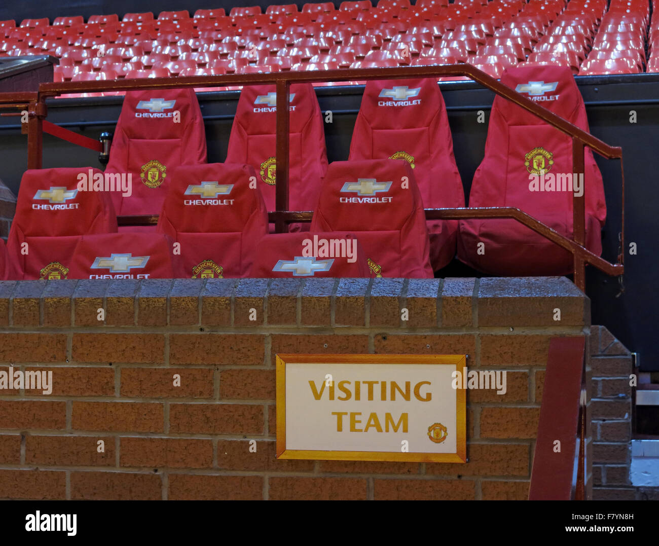 Area for visiting team at Man Utd,Old Trafford,Manchester united,England,UK,Chevrolet,red,seats - Stock Image