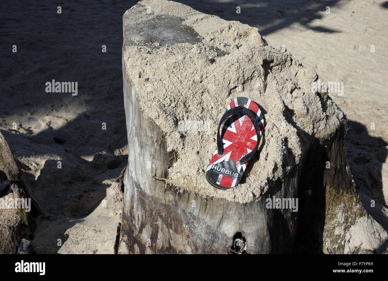 A single sandal with a GB UK Union Jack Flag design found resting on a sand covered tree stump on the beach in Pattaya - Stock Image