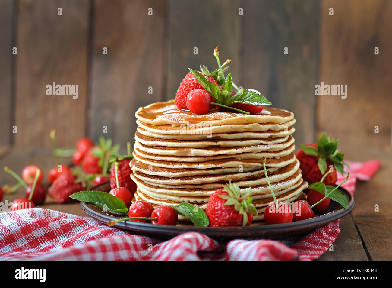 Pancakes with berries and syrup in a rustic style. - Stock Image