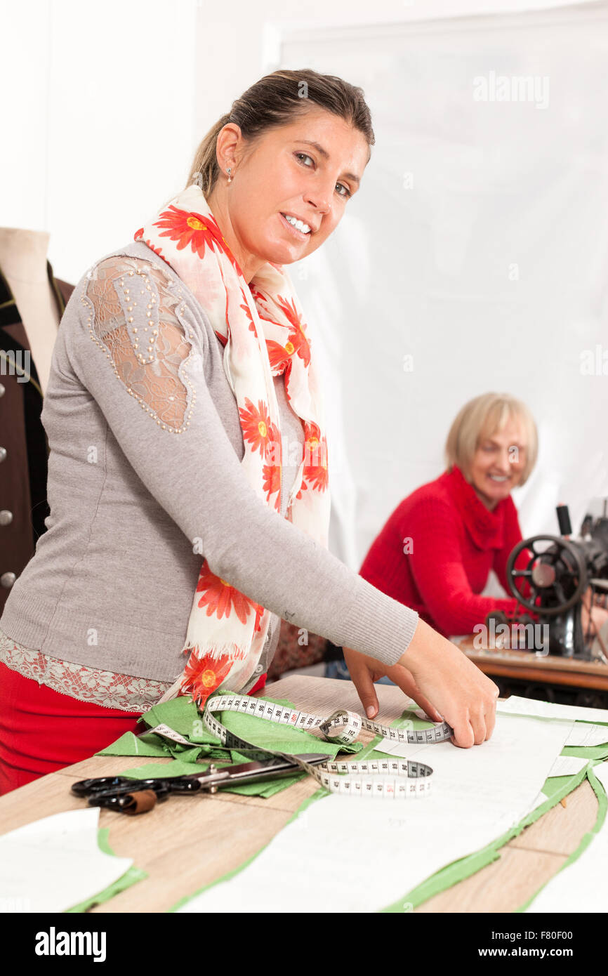 two happy seamstresses working in a taylor shop - Stock Image