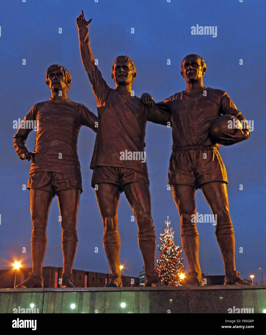 United Trinity/Holy Trinity statue of Manchester United trio of George Best, Denis Law, and Bobby Charlton at dusk - Stock Image