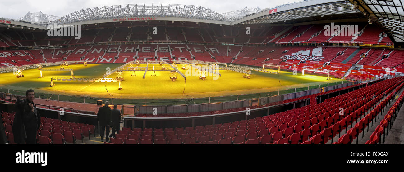 Manchester United pitch with solar lamps on grass turf in winter panorama - Stock Image