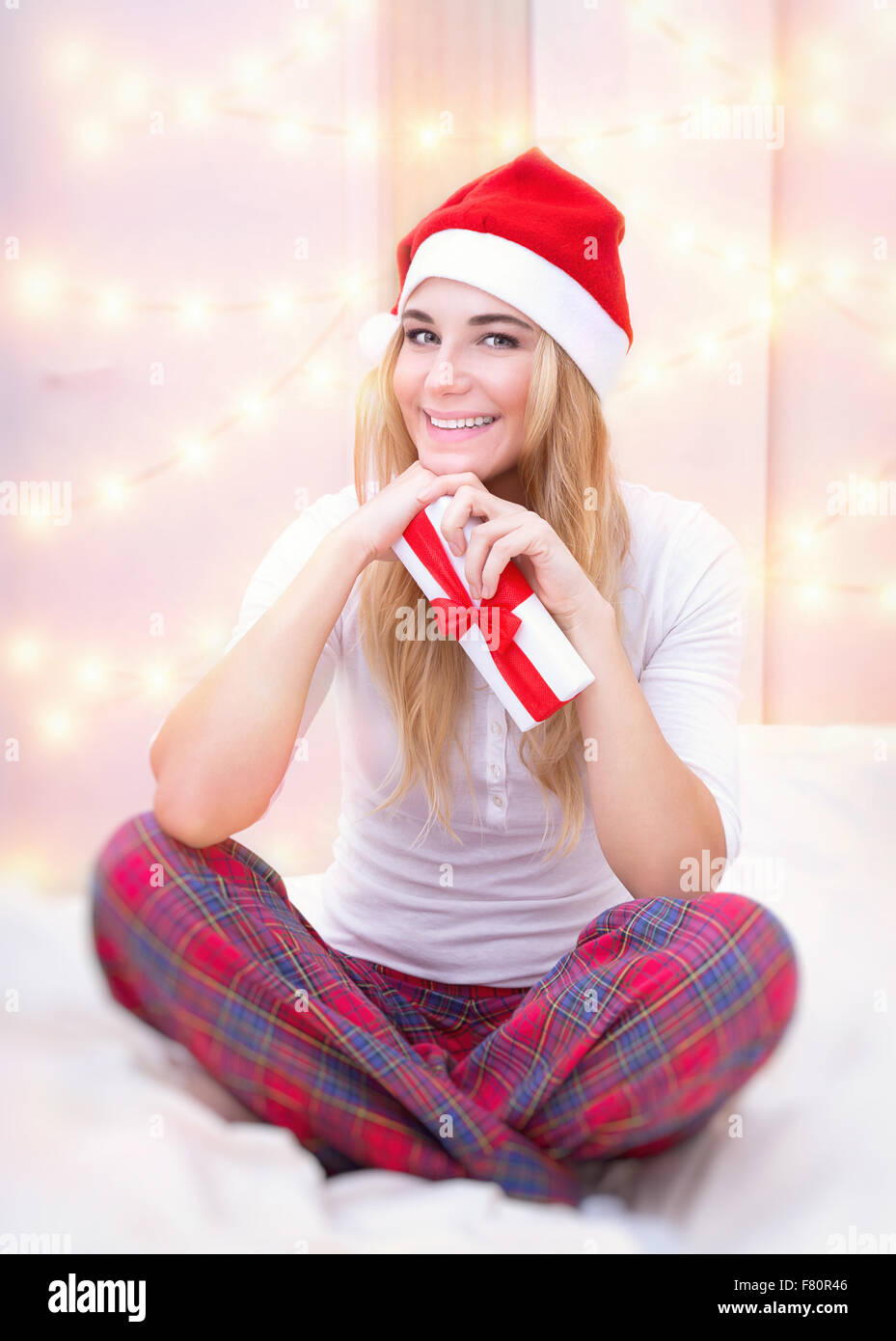 dcd33c096fe657 Cheerful woman with Christmas gift sitting on the bed at home on festive  lights background,