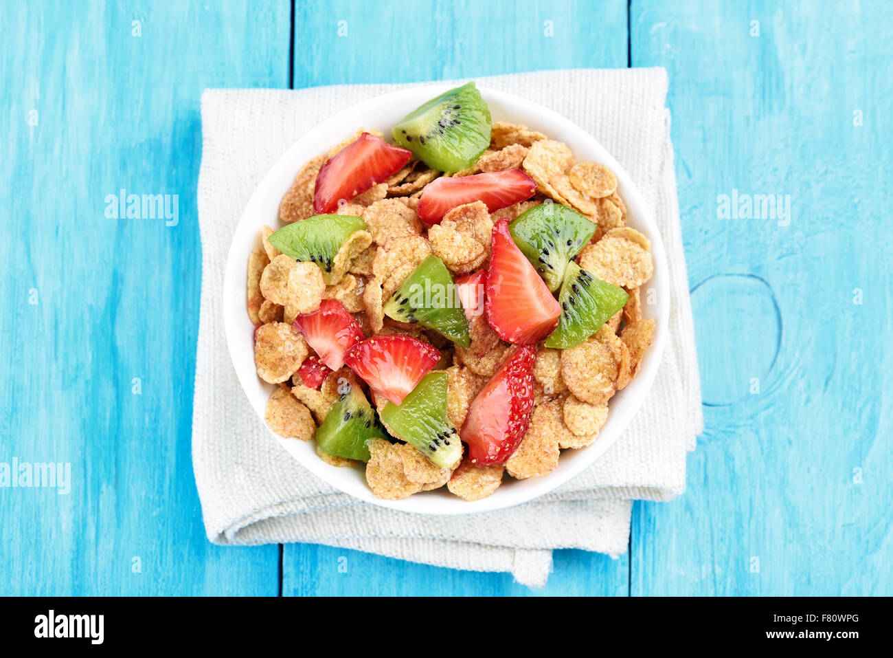 Cornflakes with fresh strawberry and kiwi, top view - Stock Image