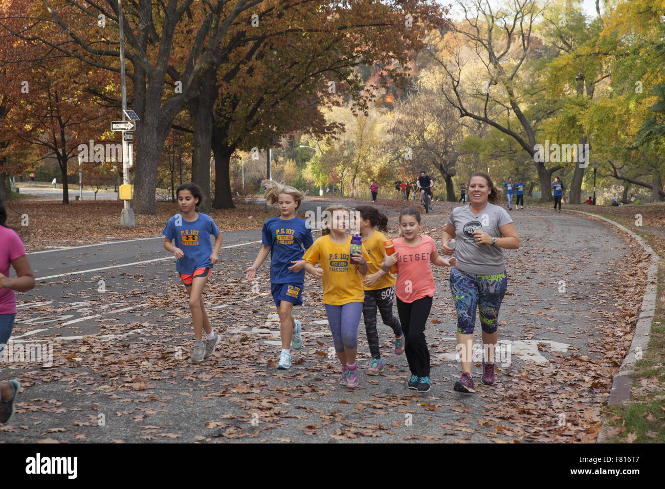 Local elementary school children jogging together on the road in Prospect Park, Brooklyn, New York. - Stock Image