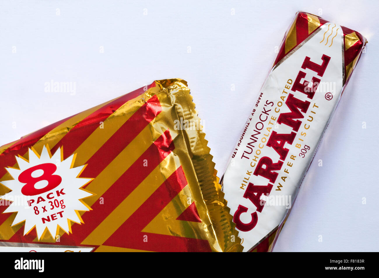 Tunnocks milk chocolate coated Caramel wafer biscuit - one removed from 8 pack wrapper packet set on white background - Stock Image