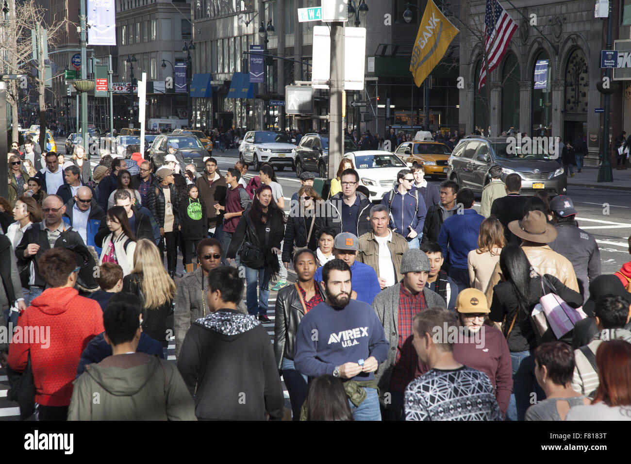 Crowds of tourists and shoppers cross 42nd St. at 5th Ave. on Black Friday the official start of the holiday shopping - Stock Image