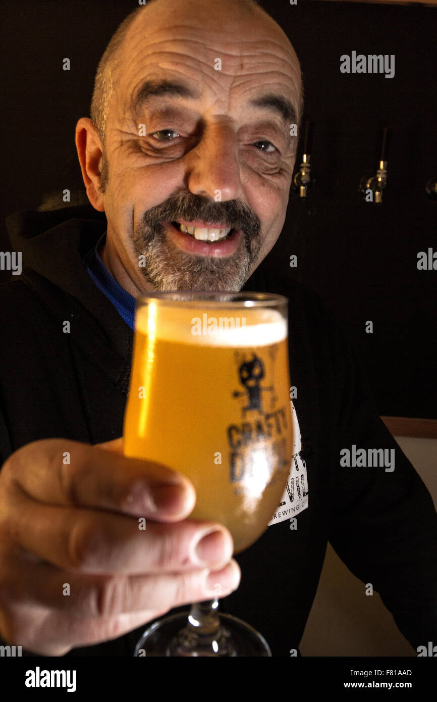Cardiff, United Kingdom, November 26 2015. Storekeeper Gareth serves up a pint at the Crafty Devil's Cellar - Stock Image