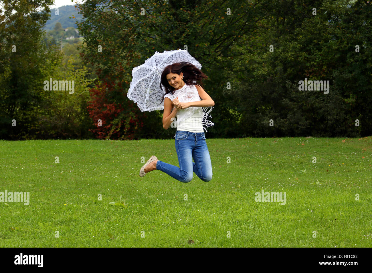 Beautiful happy brunette jumping with white lace umbrella. - Stock Image
