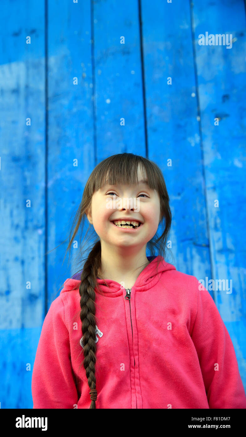 Young girl smiling on background of the blue wall - Stock Image