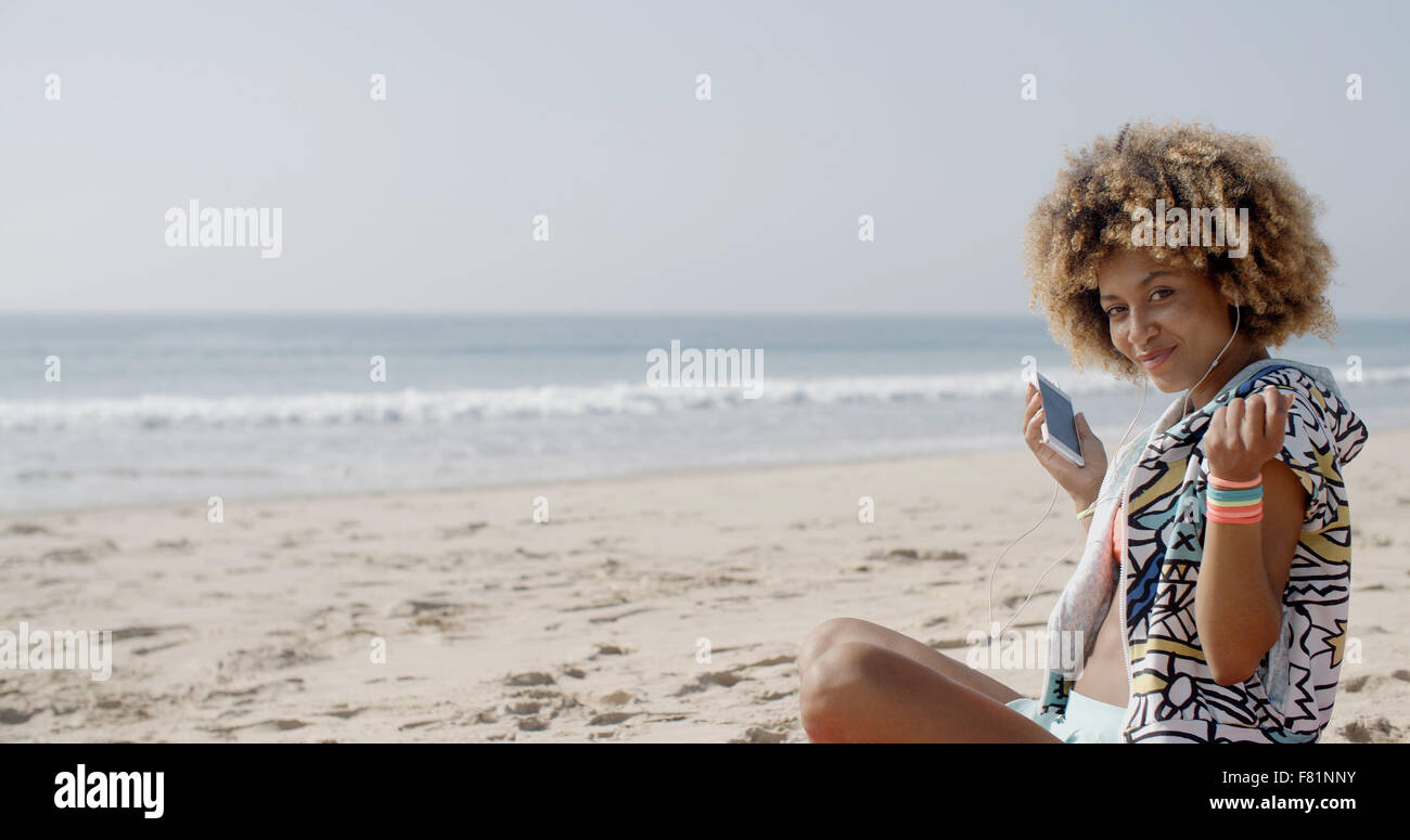 Young Woman With Earphones On The Sea Coast - Stock Image