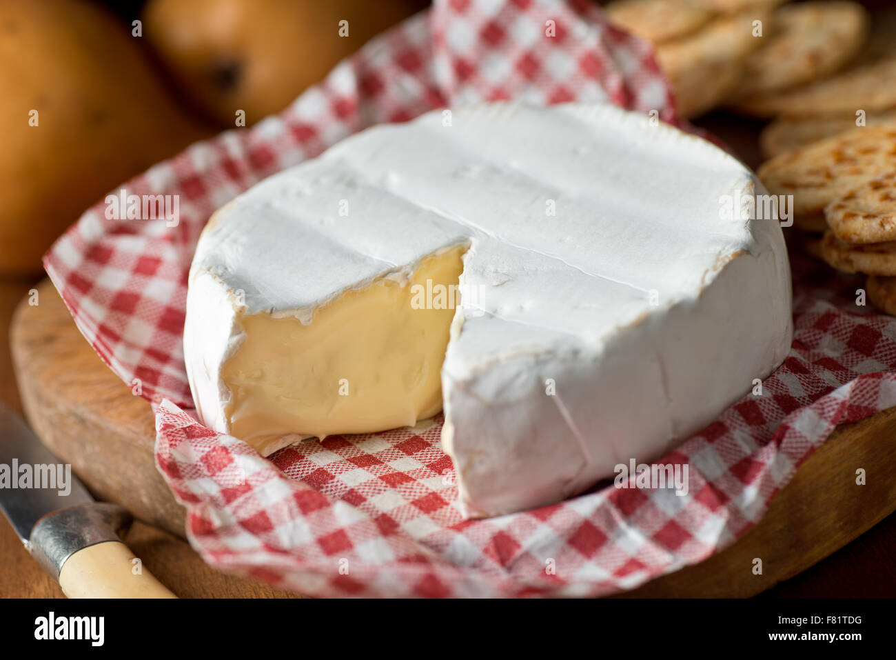 Delicious creamy wheel of brie cheese with crackers and pears. - Stock Image