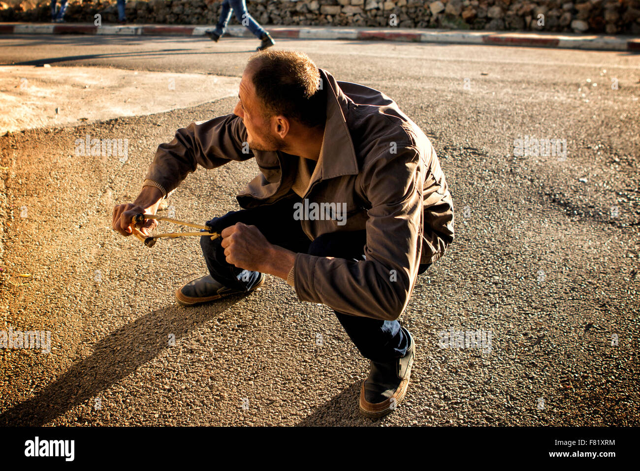 Near Ramallah, West Bank, Mideast. 4th December, 2015. A Palestinian man fires his slingshot towards Israeli soldiers - Stock Image