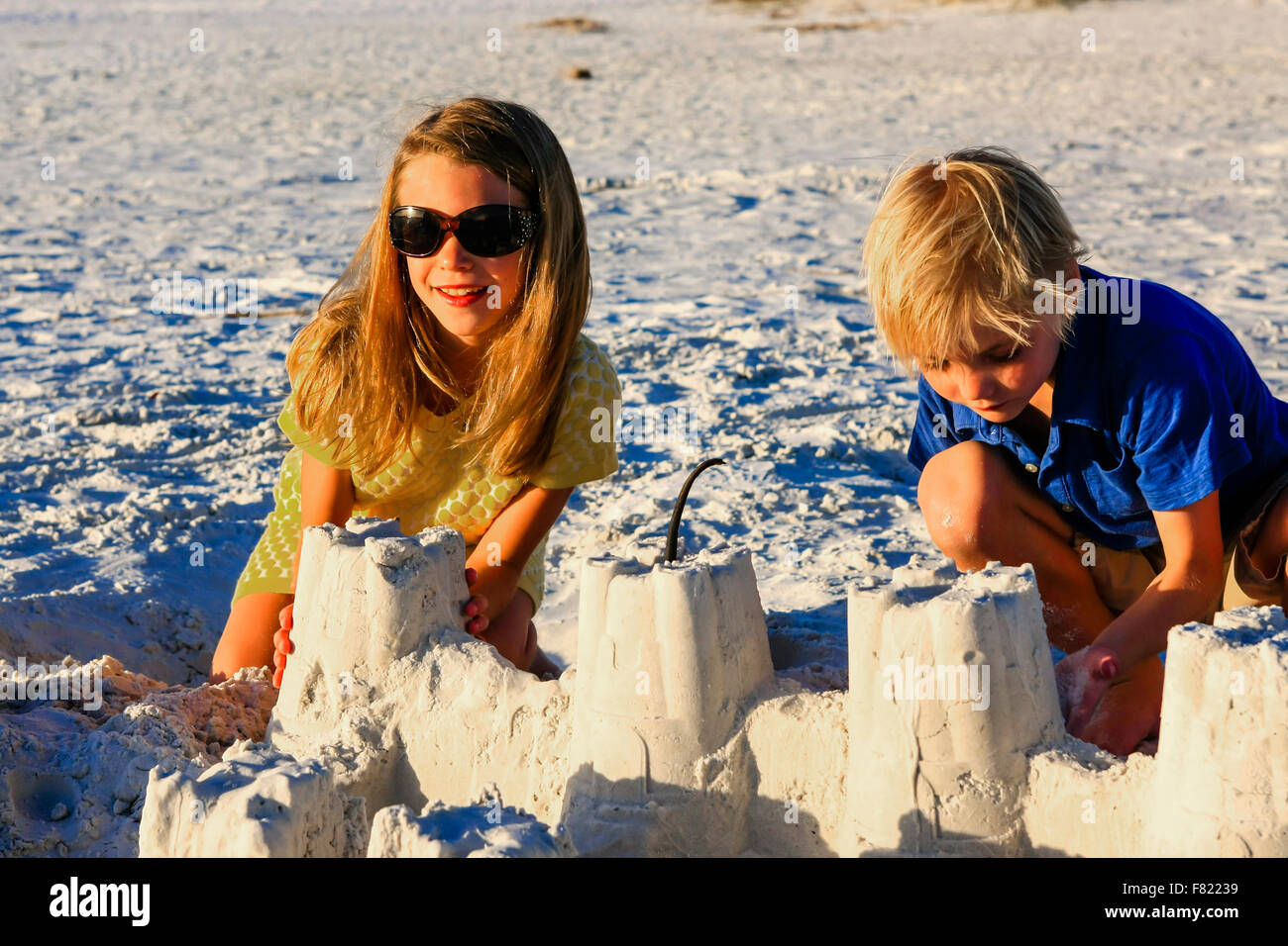 Young brother and sister posing at sunset by the sand castle they built on Siesta Key beach in Florida - Stock Image