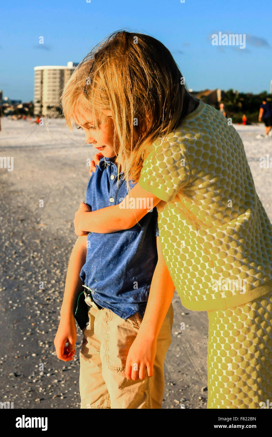 Young pre-teen sister giving her younger brother a hug on Siesta Key beach in Florida - Stock Image