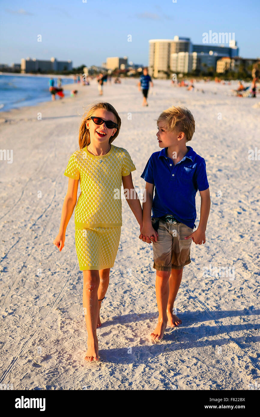 Young pre-teen girl and her brother holding hands as they walk along Siesta Key beach in Florida - Stock Image