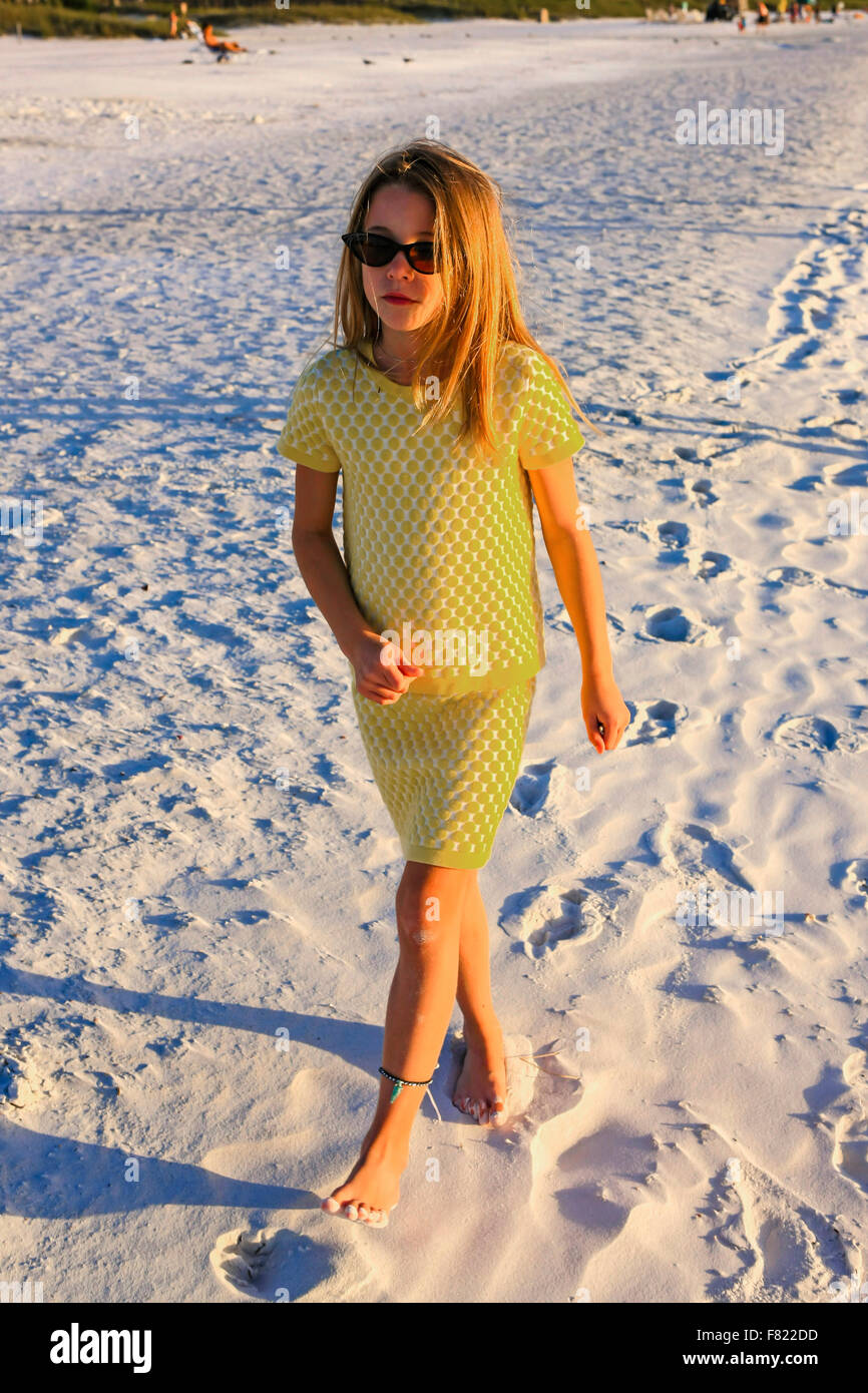 Young pre-teen girl wearing a yellow two-piece at sunset on Siesta Key beach in Florida - Stock Image