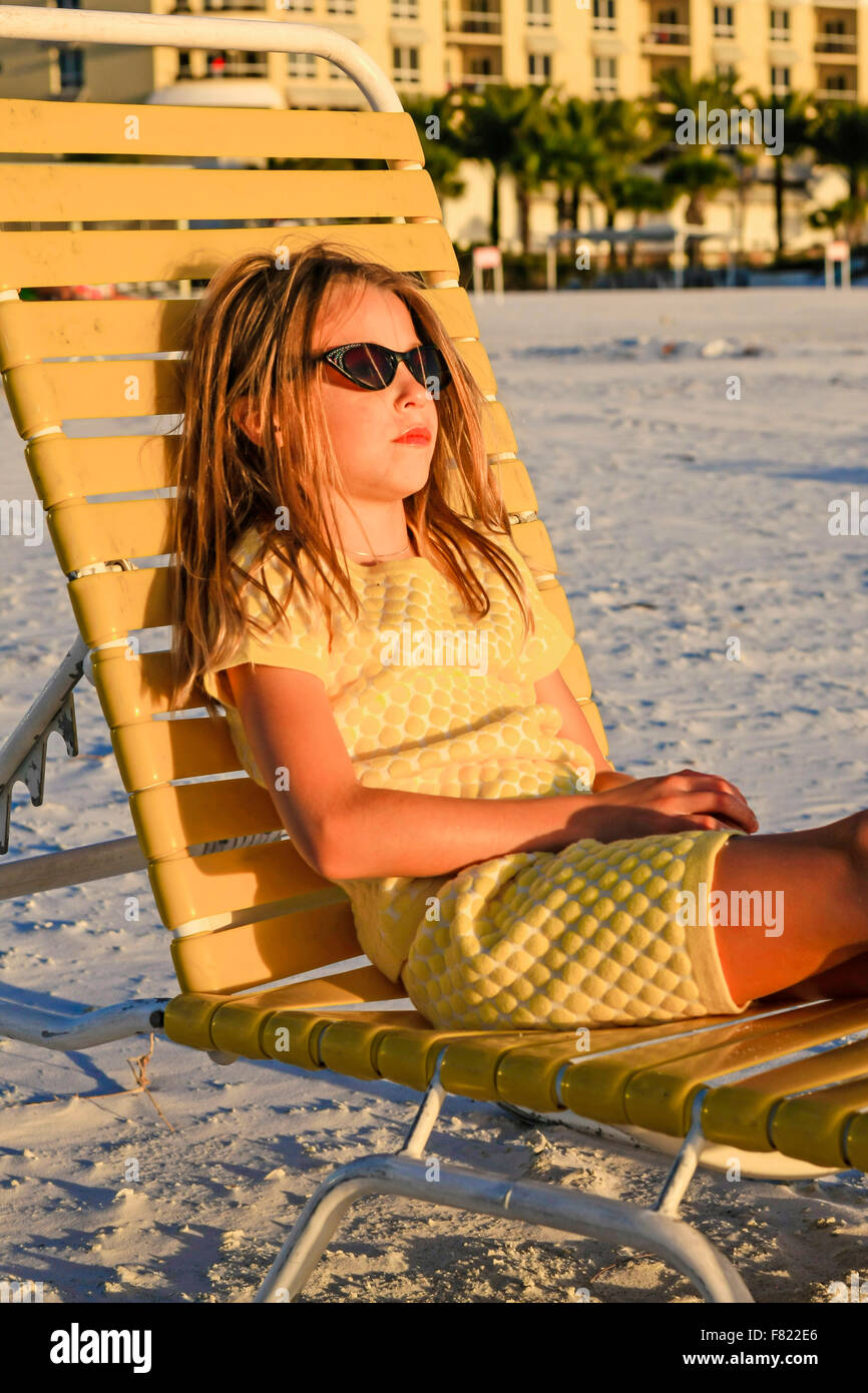 Young pre-teen girl sitting on a beach lounger watching the sunset at Siesta Key, Florida - Stock Image