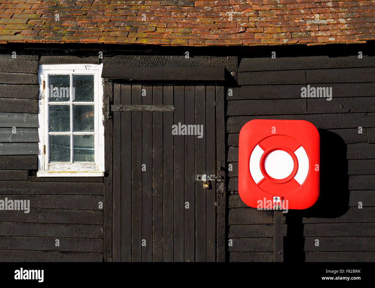 Lifebelt mounted on wooden building in the village of Bosham, Sussex, England UK - Stock Image