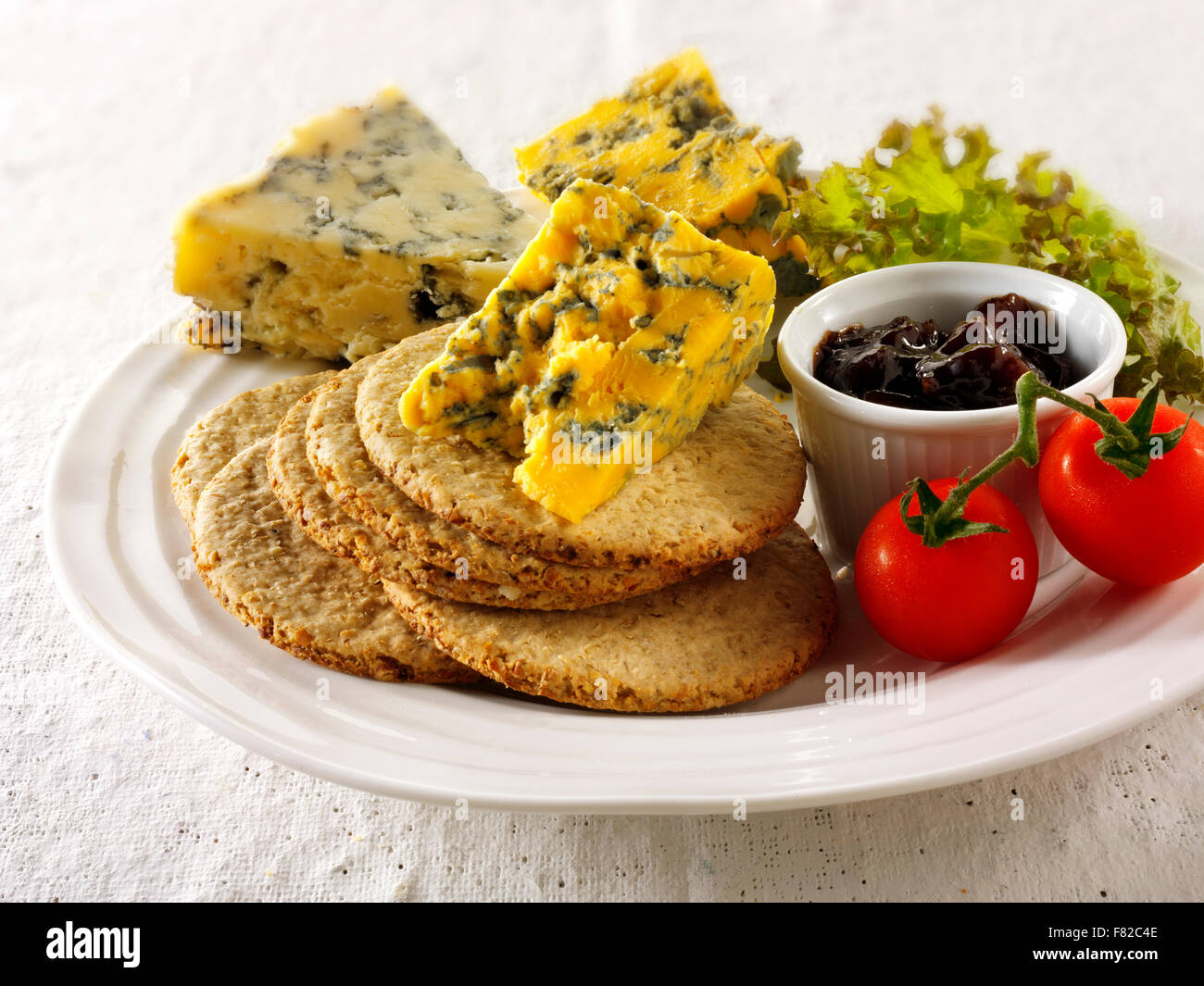 Blue cheese & biscuits with stilton, white stilton & blacksticks cheese. Served on a plate - Stock Image