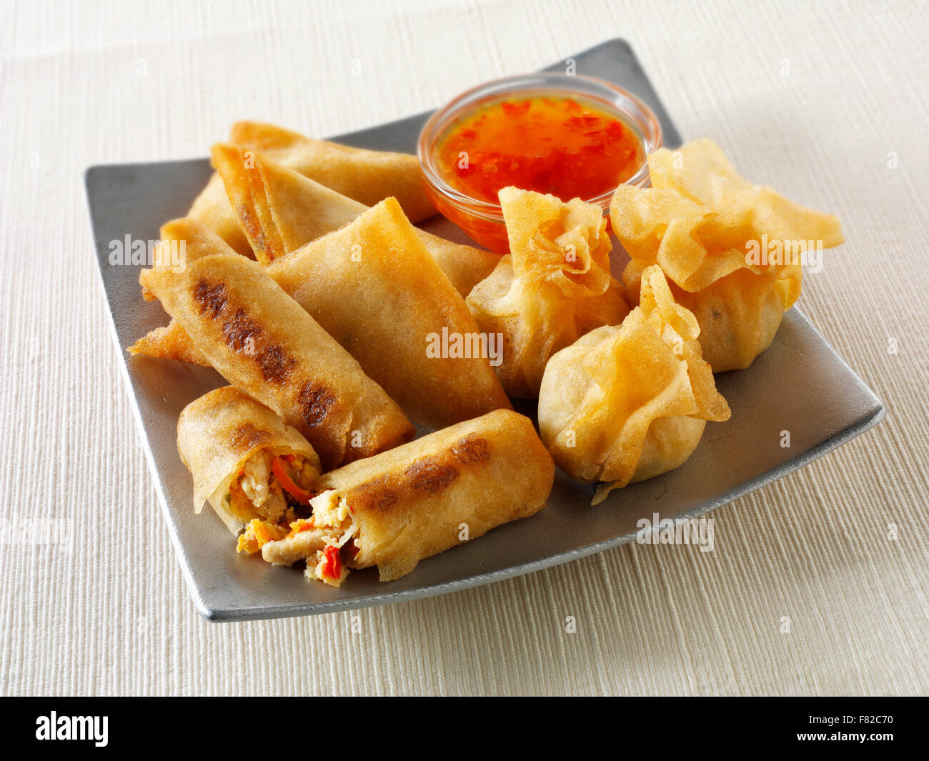 Oriental selection with dim sum,  spring rollswith chicken & vegetables and vegetable samosas with a chilli - Stock Image