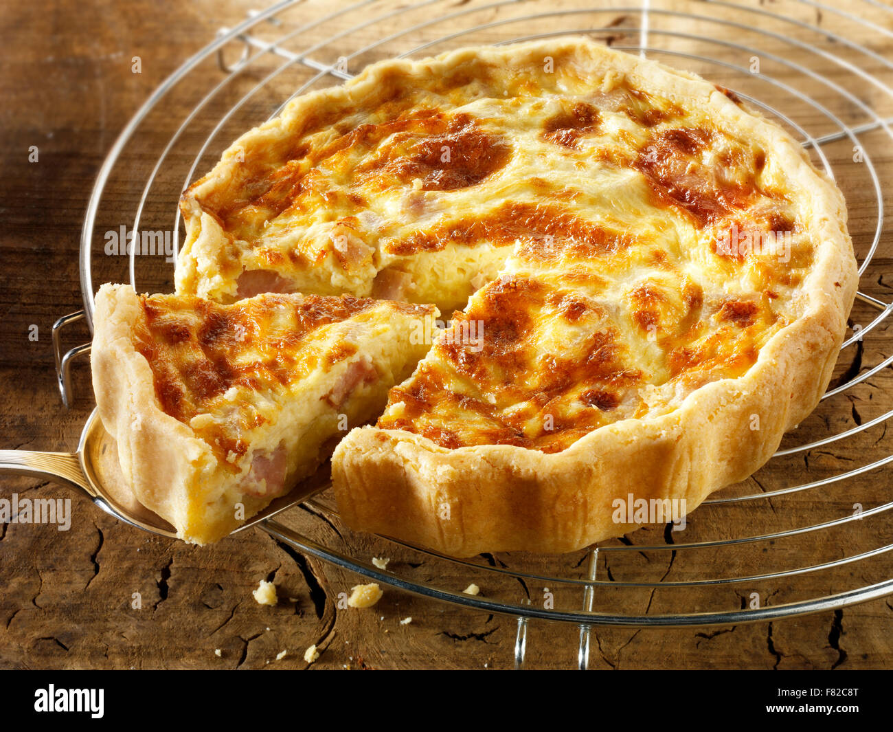 Whole quiche Loraine in a lunch time setting with a cut slice Stock Photo