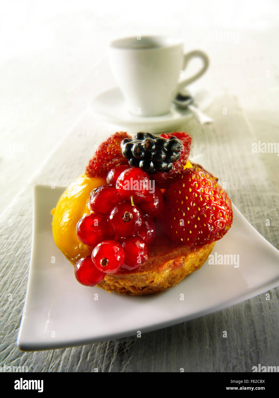 Artisan Patissier fruit cake with redcurrants, wild strawberries, blackberry and creme patisserie in a light sponge - Stock Image