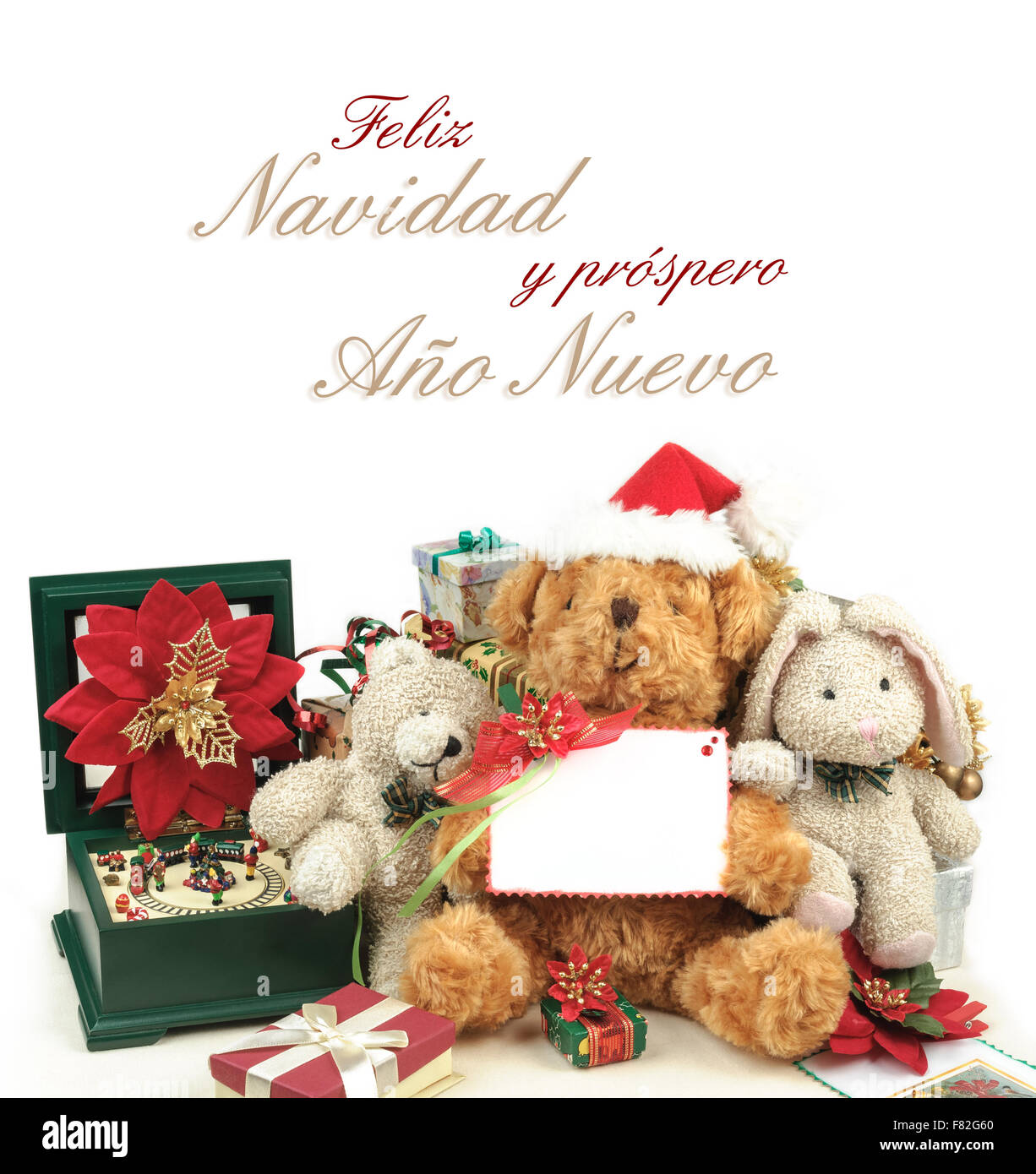 Christmas greeting card with teddy bear, toys & gifts, the text Feliz Navidad y prospero Año Nuevo and - Stock Image