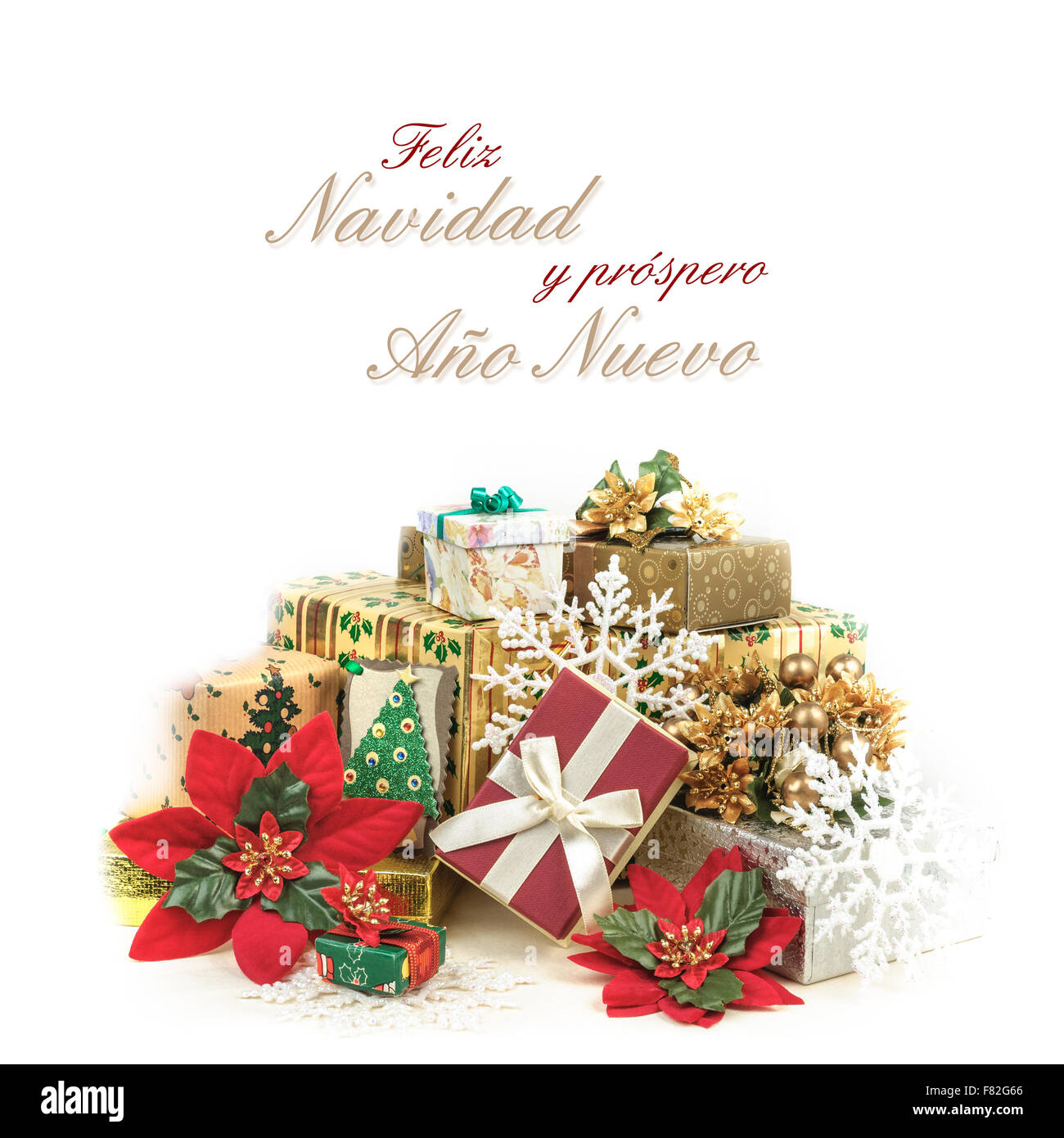 Christmas greeting card with pile of gifts in colorful wrapping and the text Feliz Navidad y próspero Año - Stock Image