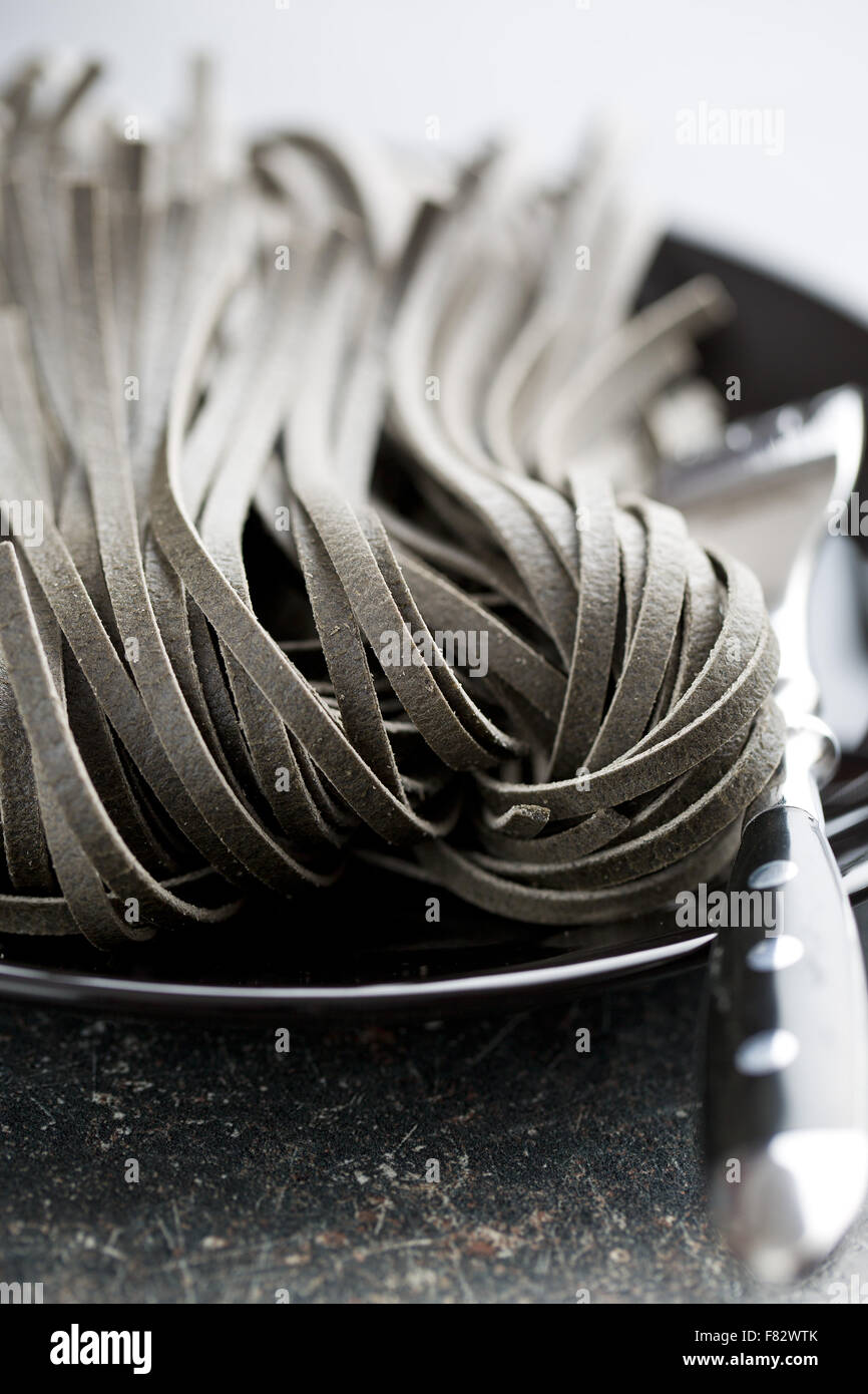 black uncooked noodles with squid sepia ink - Stock Image