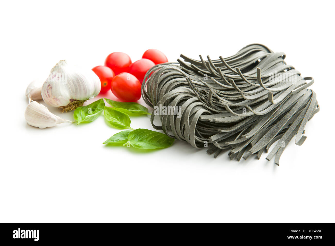noodles, garlic, tomatoes and basil leaves on white background - Stock Image
