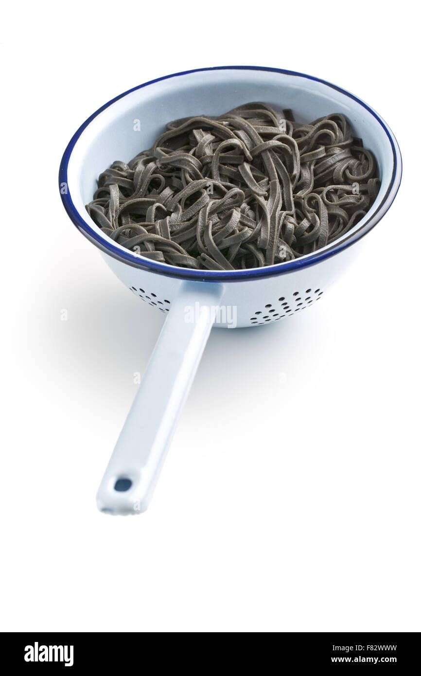 cooked black noodles with squid sepia ink in colander - Stock Image