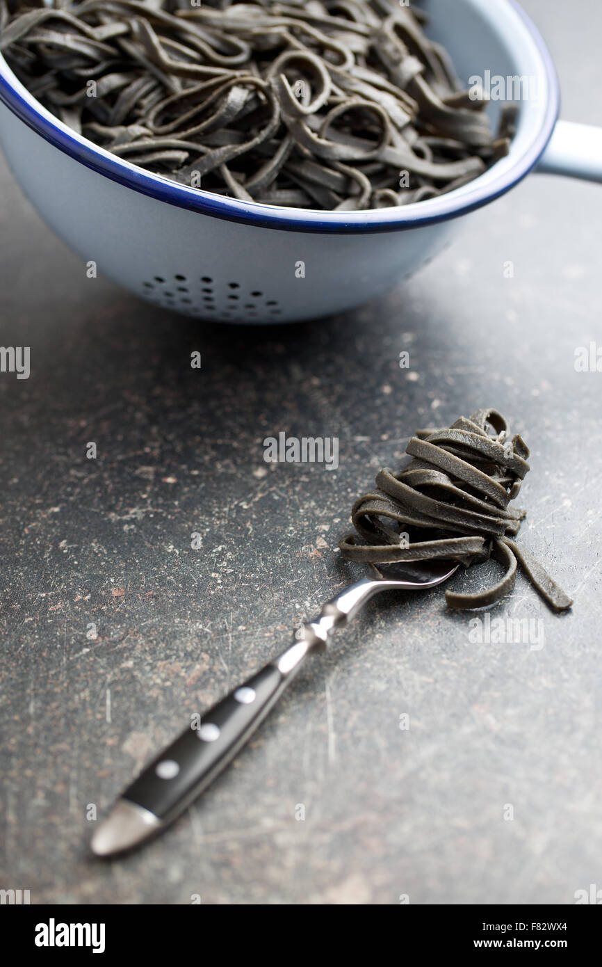 cooked black noodles with squid sepia ink on fork - Stock Image