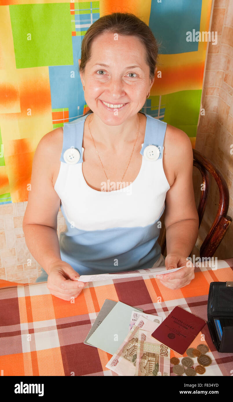 Happy mature woman with bill and money at her home - Stock Image