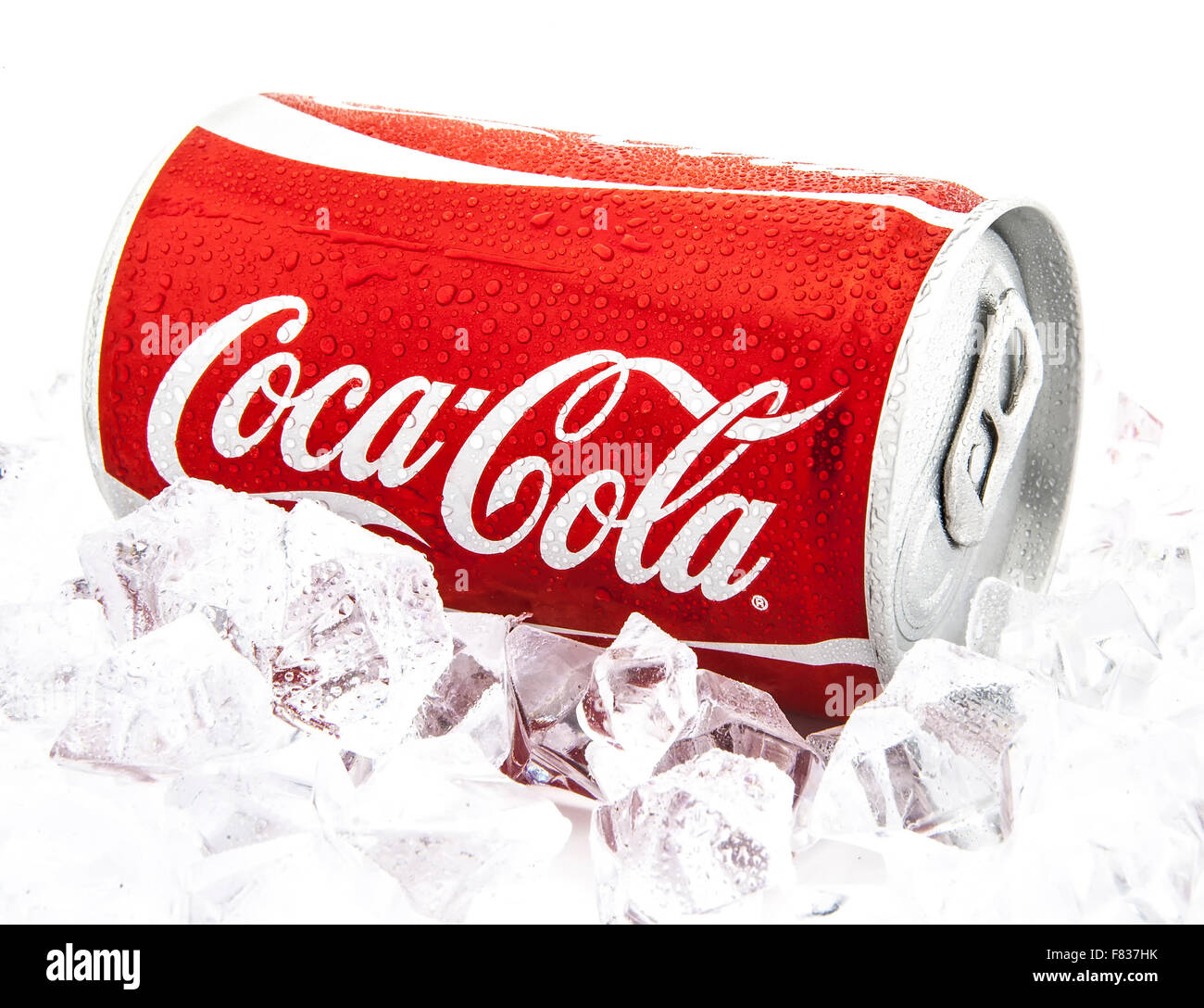 Can of Coca-Cola on a bed of ice over a white background - Stock Image