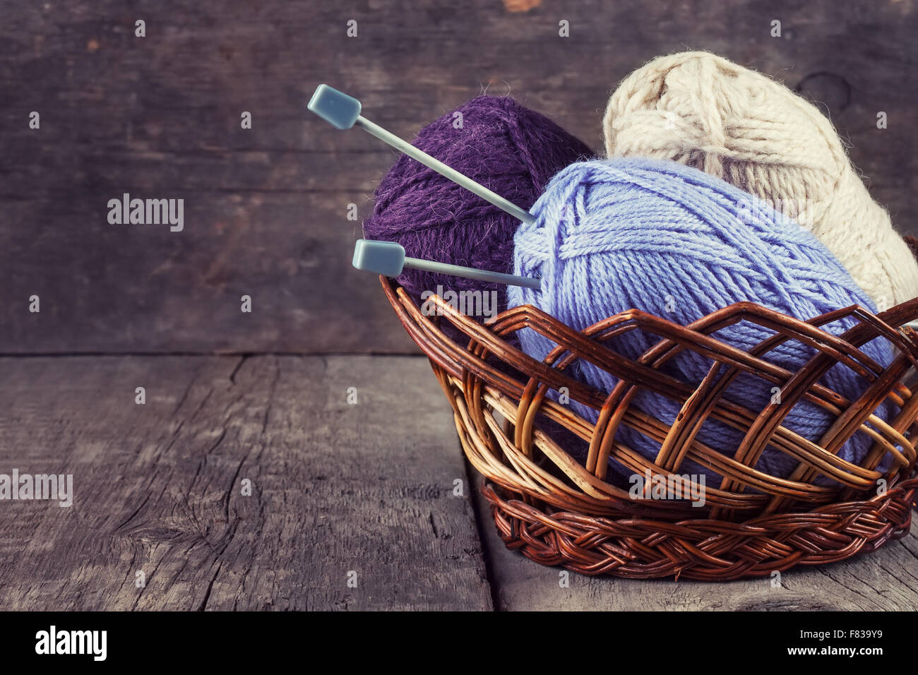 Skeins colored yarn and knitting needles in a basket on a wooden background - Stock Image