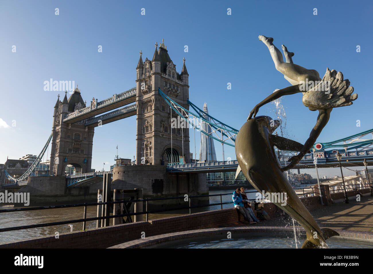 Girl and dolphin statue with Tower Bridge behind at London, UK Stock Photo