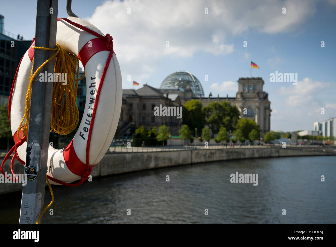 Feuerwehr (Fire brigade) on a lifebelt or lifebuoy on a bridge over the river Spree with the German Reichstag in - Stock Image
